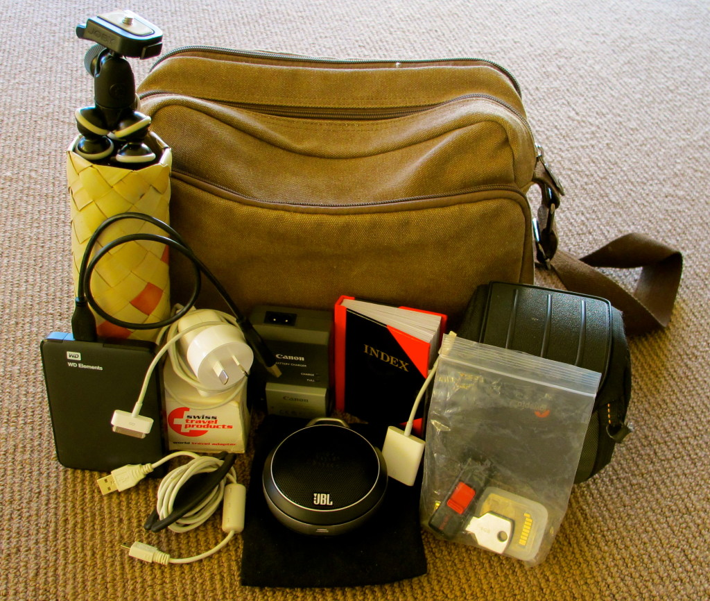 Camera, tripod, multi-foreign adaptor, chargers, portable speakers, index book, back up drive, memory cards and sticks