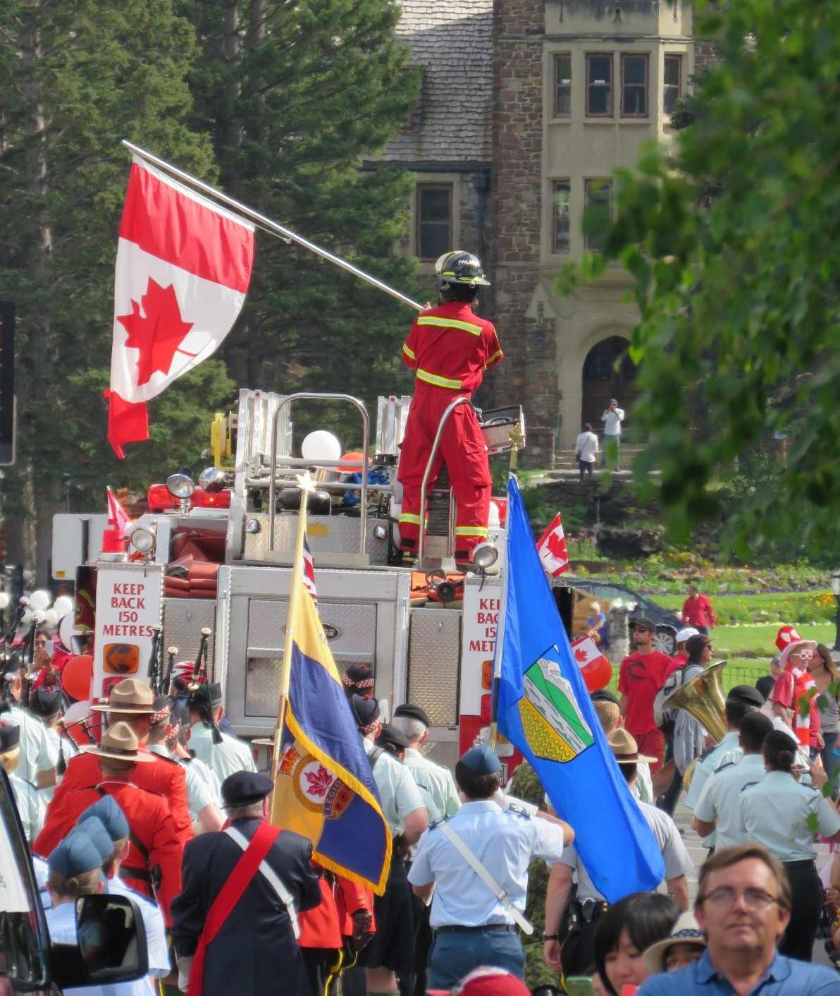 Canadian firefighter waving the Canadian flag, Canada Day, Banff, Canada